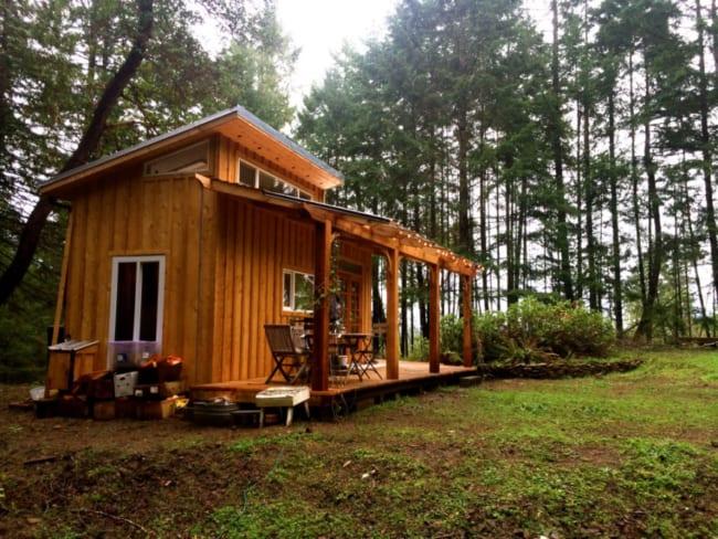 Casa de madeira pequena com luzes na varanda